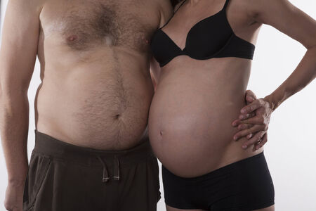 female pose: embraced pregnant woman and fat man on white background