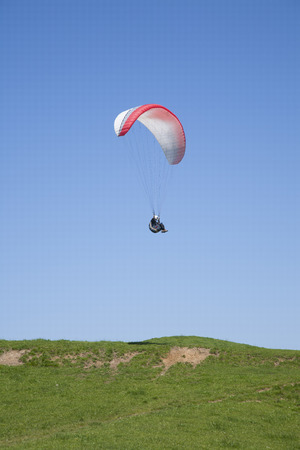 paraglider flying over green field in Asturias Spain photo