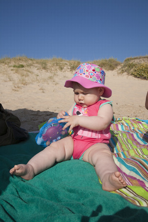 baby with pink hat sitting on green towel at beach photo