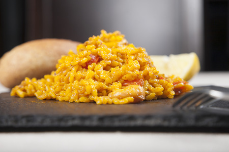 close up tapa of spanish paella on black slate plate photo
