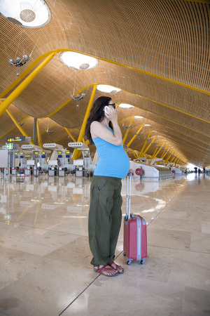 woman pregnant talking phone in airport hall