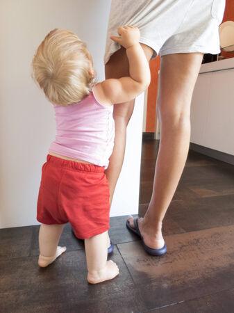 blonde baby red shorts clutching mom leg in white kitchen photo
