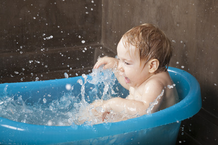 nude baby: blonde naked baby washing in blue little bath indoor with brown background