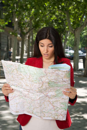 angry brunette woman watching a map at street in Madrid city Spain photo