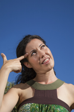gesticulating: woman gesticulating crazy finger symbol in head Stock Photo