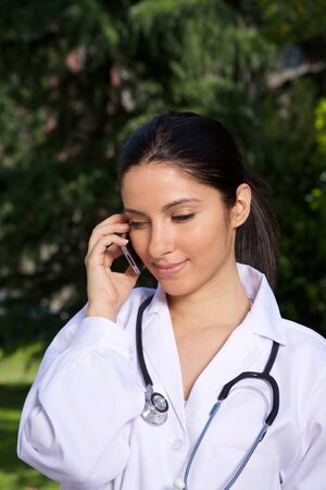 doctor young woman talking mobile over a green trees background photo
