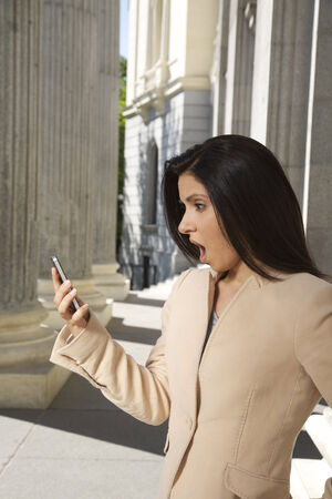 portrait of shocked woman looking at smartphone photo