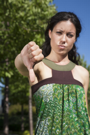 woman with thumb down in exterior background photo