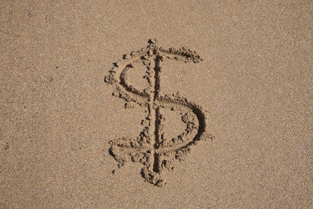sand dollar: Dollar symbol written on brown sand ground low tide beach seashore Stock Photo