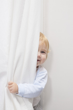 white curtain: blonde baby sixteen month old peeking face behind white curtain