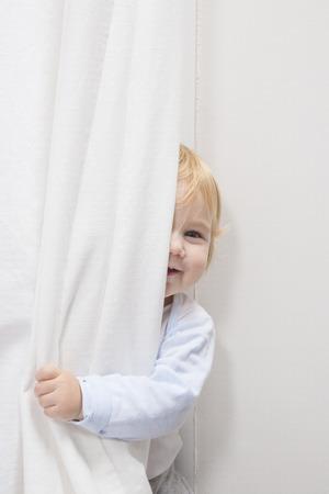 blonde kindje zestien maanden oude gluren gezicht achter wit gordijn