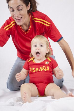 celebrating blonde baby sixteen month old with red shirt of Spanish soccer team and mother photo