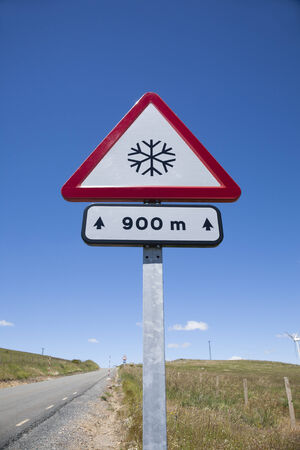 rural road: metal pole with traffic signal advice danger snow at 900 metres in rural road next to Madrid Spain Europe Stock Photo