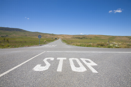 rural road: crossroad with stop symbol white painted on asphalt in rural road next to Madrid Spain Europe Stock Photo