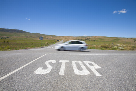 rural road: crossroads with stop symbol white painted on asphalt and fast car in rural road next to Madrid Spain Europe