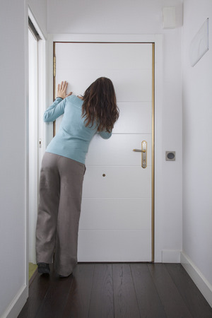 peephole: brown trousers green jersey woman back looking to peephole interior house hall white door wooden floor Stock Photo