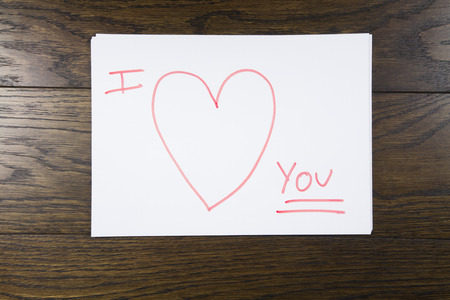 bliss: I love you text written with orange marker on white paper over brown wooden background