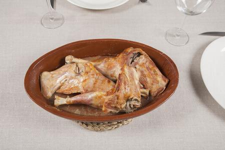 Español pierna asada de cordero lechal en la bandeja de cerámica en el mantel de lino marrón Foto de archivo - 35001849
