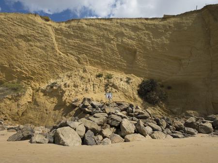 steep cliffs sign: landslides hazard signal spanish advice danger in coastline cliff next to Conil Cadiz Spain Europe