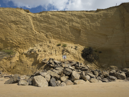 coastline: landslides hazard signal spanish advice danger in coastline cliff next to Conil Cadiz Spain Europe