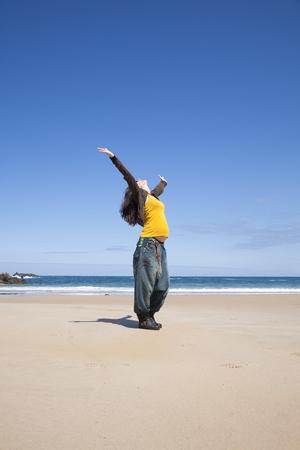 yellow shirt: arms up pregnant woman with yellow shirt at Asturian beach