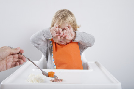 highchair: blonde caucasian baby seventeen month age orange bib grey sweater eating meal in white high-chair with hands on eyes does not like carrot