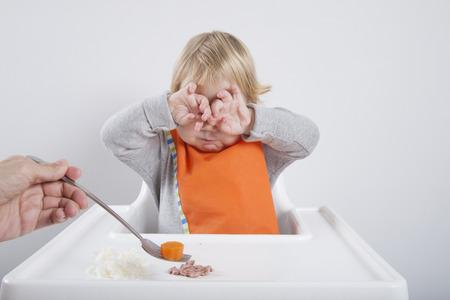 babero: rubia caucásica bebé diecisiete meses de naranja edad babero comida suéter gris comer en blanco de alta silla con las manos en los ojos no le gustan zanahoria Foto de archivo