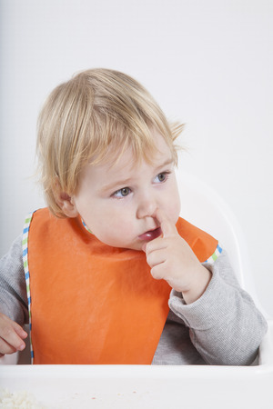 snot: blonde caucasian baby seventeen month age orange bib grey sweater sitting on white high-chair eating with finger picking nose