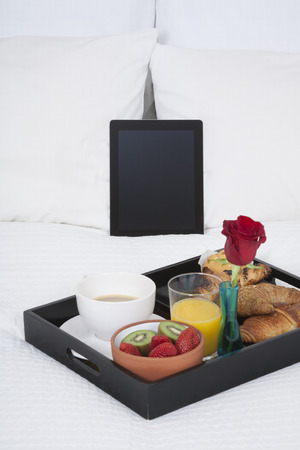 white quilt bed breakfast black tray croissants orange juice strawberry kiwi cupcake red rose flower and digital tablet blank screen photo