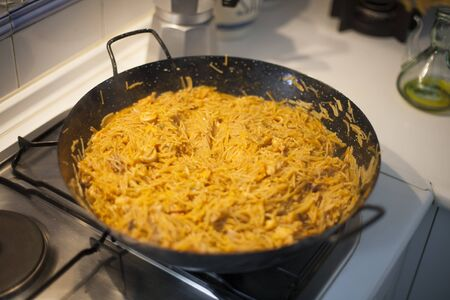 kitchen spanish: black pan with fideua typical spanish food with noodles cooked as a paella on fire of kitchen