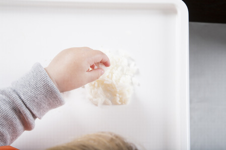 baby rice: blonde caucasian baby seventeen month age orange bib grey sweater eating rice with her hand in white high-chair