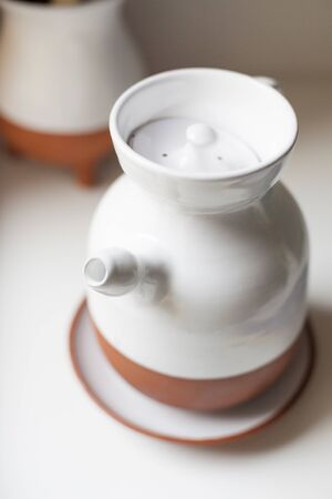 oilcan: ceramic white and orange jug with spout and top cover on a plate for olive oil to cook in the kitchen
