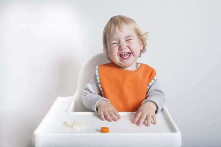 baby rice: blonde caucasian baby seventeen month age orange bib grey sweater eating rice carrot on white high-chair laughing and smiling