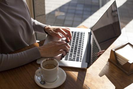 klawiatura: brunetka fioletowe sweter kobieta pisania klawiatury pc laptop z białym mała filiżanka cappuccino na lekkim brązowym drewnianym stole kawiarni Zdjęcie Seryjne