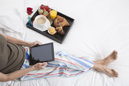 woman green shirt striped pajama pants sitting on white bed with digital tablet blank screen and breakfast tray croissants orange juice strawberry kiwi cupcake red rose flower Stock Photo