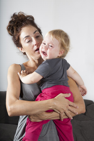 lament: portrait of one year age blonde lovely cute caucasian white baby grey shirt pink trousers looking at camera face indoors crying and scream shout with tears eyes in brunette woman mother arms embrace hug