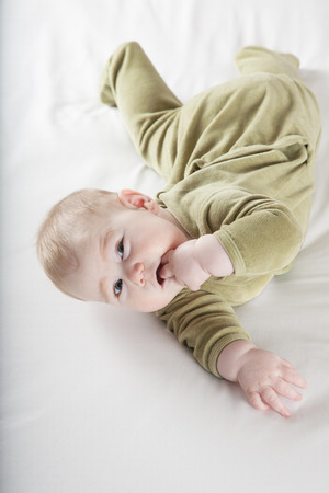 six months: six months age blonde baby green velvet lying on white sheet bed smiling happy face Stock Photo