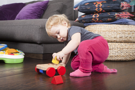 shocks: one year age blonde lovely cute caucasian white baby grey shirt pink trousers and shocks playing with wheel wooden colors toys indoor on brown floor Stock Photo