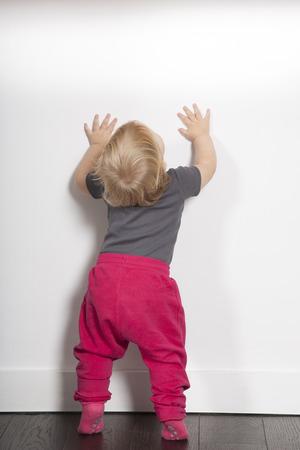 een jaar oud blonde mooie schattige Kaukasische witte baby grijze overhemd roze broek en schokken staan indoor op bruine vloer tegen een witte muur kijken kopie ruimte