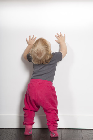 one year age blonde lovely cute caucasian white baby grey shirt pink trousers and shocks standing indoor on brown floor against white wall looking up copy space