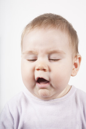 revulsion: portrait of eight months age blonde lovely cute baby pink velvet onesie disgusted or sneeze face isolated on white