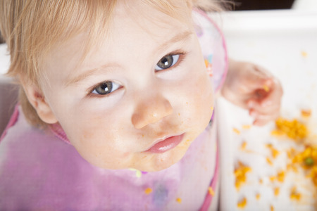 baby rice: overhead shot of one year age caucasian baby pink plastic bib eating meal yellow orange rice paella with her hand in white high-chair