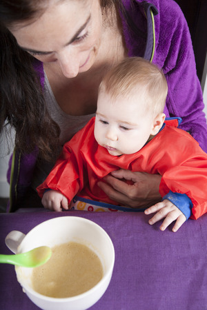 six months: six months age blonde caucasian baby red bib in woman mother purple velvet jacket arms eating puree
