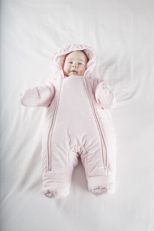 six months age cute baby dressed up in pink fluffy winter snowsuit snug hoodie clothes lying on white sheet bed smiling happy face photo