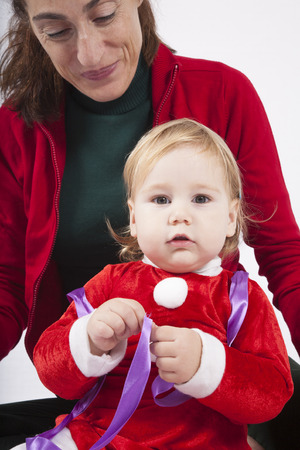 red cardigan: one year age caucasian blonde baby Santa Claus disguise with brunette woman mother red cardigan green trousers opening silver wrapped paper box gift Christmas on white background