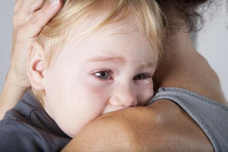 ritratto di uno anno di età bionda camicia grigia cute caucasica baby bianco bello guardare la faccia piangere e urlare urlare con le lacrime agli occhi in bruna braccia donna madre abbracciare abbraccio Archivio Fotografico