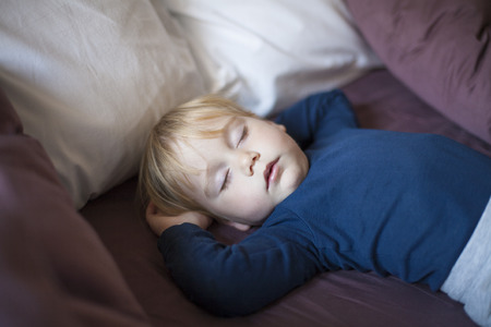 somnolent: portrait of happy blonde caucasian baby nineteen month age with blue shirt sleeping in brown sheets bed between cushions Stock Photo
