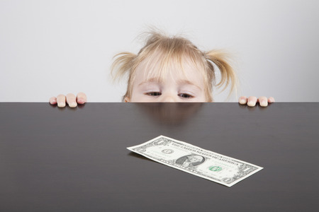 avarice: portrait of blonde caucasian baby nineteen month age with pigtails chubby face yellow shirt looking at dollar banknote on brown table horizontal