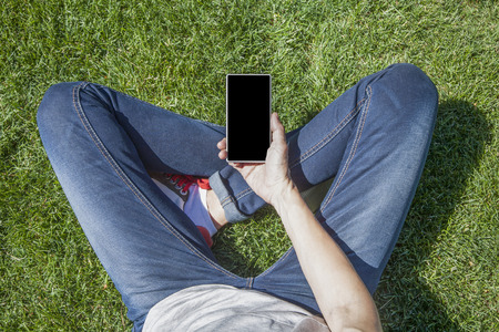 legged: hand of woman blue jeans trousers legged with mobile phone smartphone blank screen sitting on green grass lawn in park