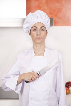 an oath: portrait of serious brunette chef woman with professional jacket and hat in white and orange kitchen saluting oath with big metal knife on chest Stock Photo
